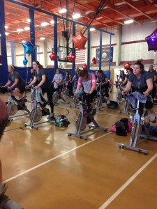 Group of participants riding their spin bikes in the open gym area