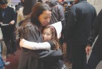 Graduate receiving a hug from a child