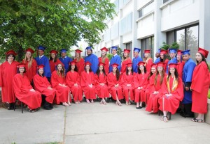 Group of graduates and red and blue caps and gowns outside the Gardner campus