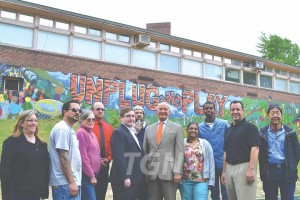 Group of students, faculty, community leaders in front of the mural