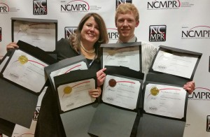 Lea Ann Scales, Vice President of External Affairs, Communications and K-12 Partnerships and Brett Moulton, Web and New Media Specialist, with the college's nine NCMPR Medallion Awards.