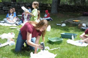 Jess Higbee working on an art project in the grass with kids in the background