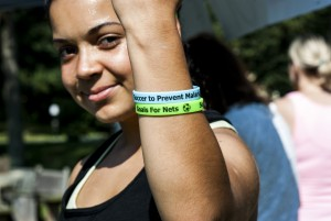 Girl holding up her write with Goals for Nets bracelets on it